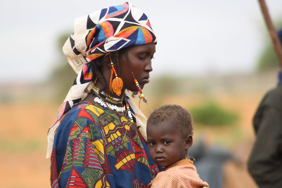 <p>A woman with her child travel on a donkeyinNiger</p>